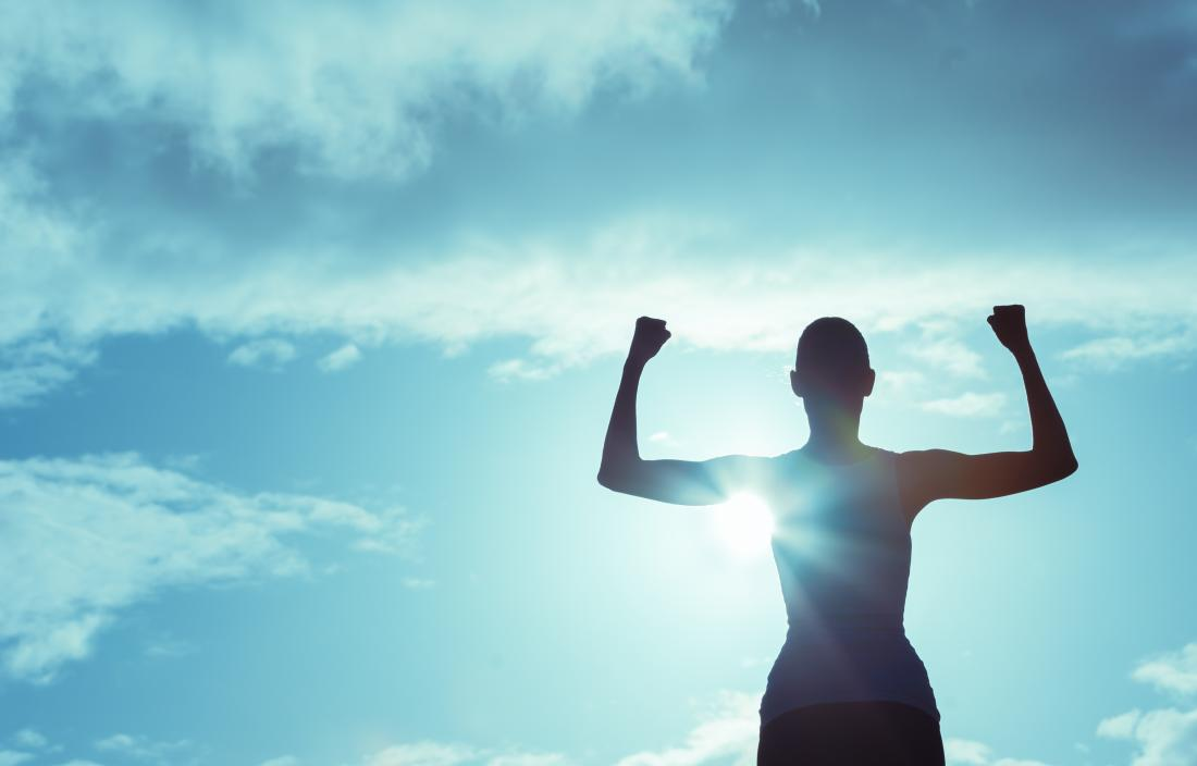 silhouette of a woman looking victorious