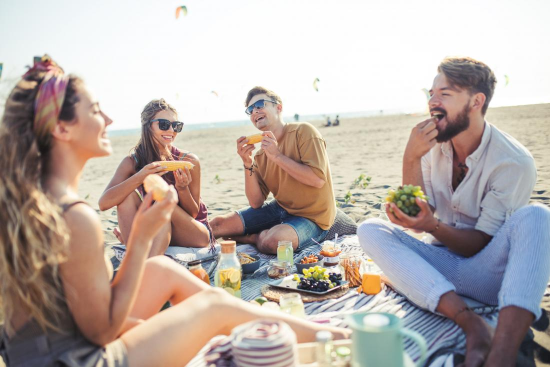 group of friends eating picnic on beach