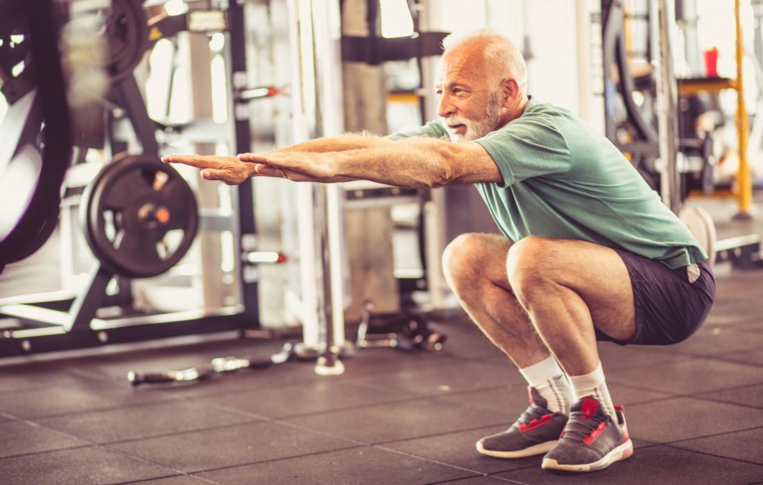 Senior man stretching during warmup in gym