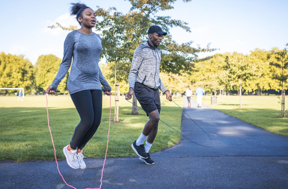 Two people in park jumping rope or using skipping rope for exercise