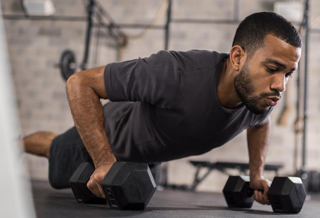 Man in gym doing pushups holding weights