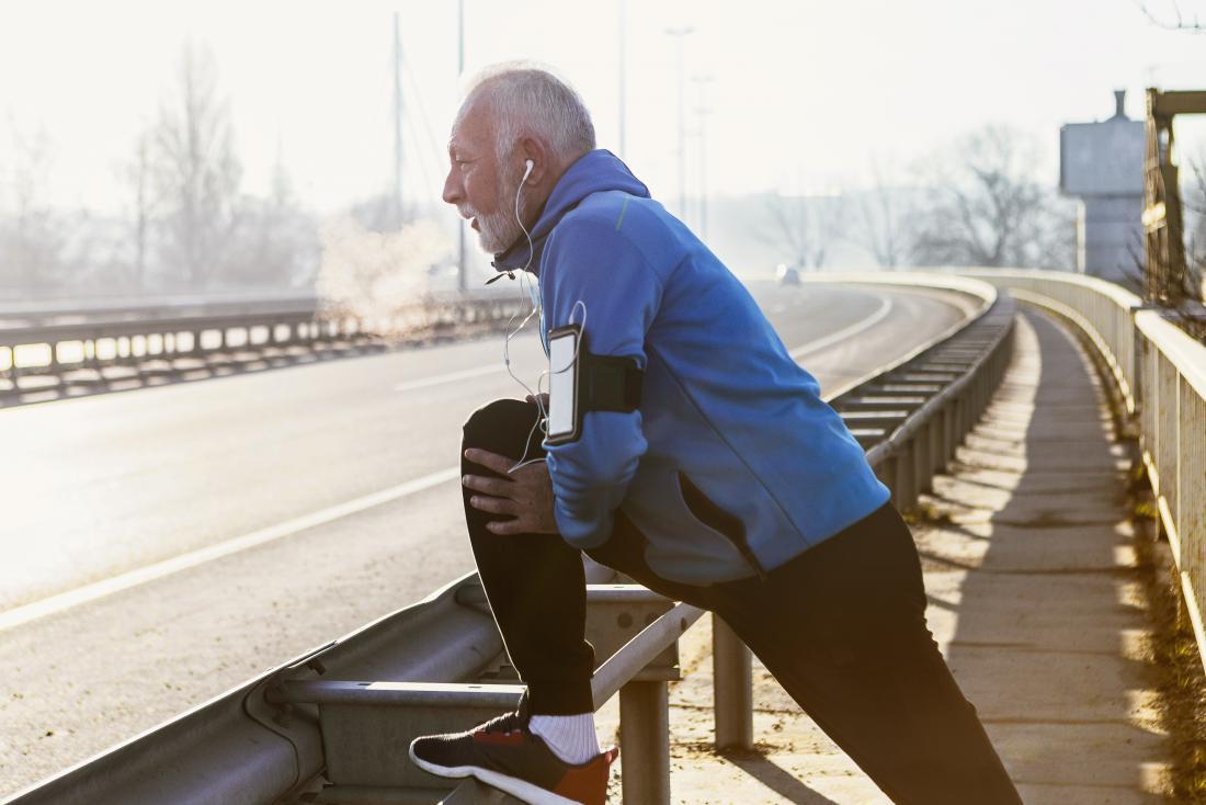 senior man stretching legs while outdoors running or jogging