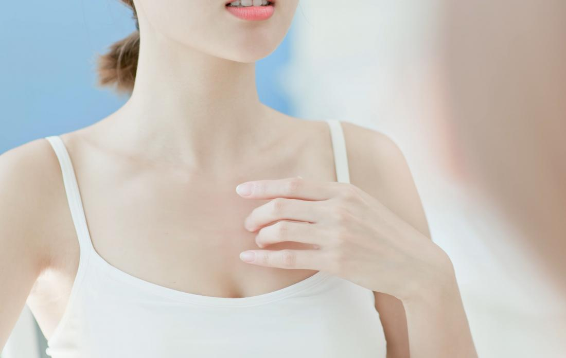 Woman looking in the mirror with hand on chest
