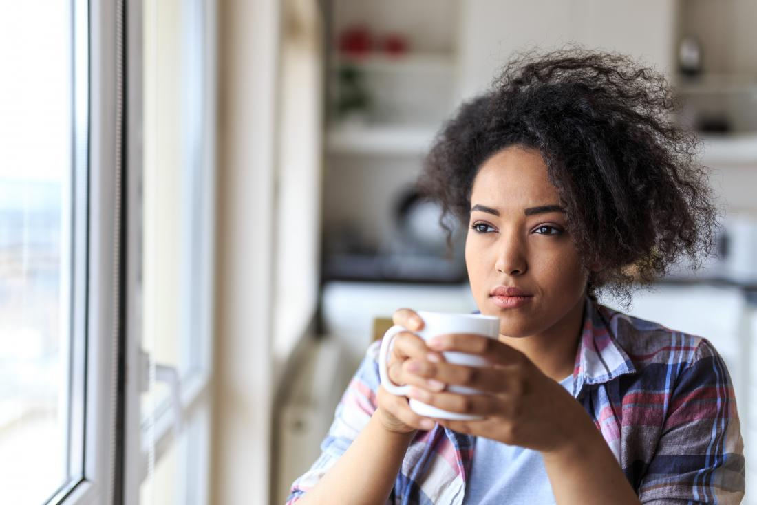 Thoughtful woman sitting down drinking tea