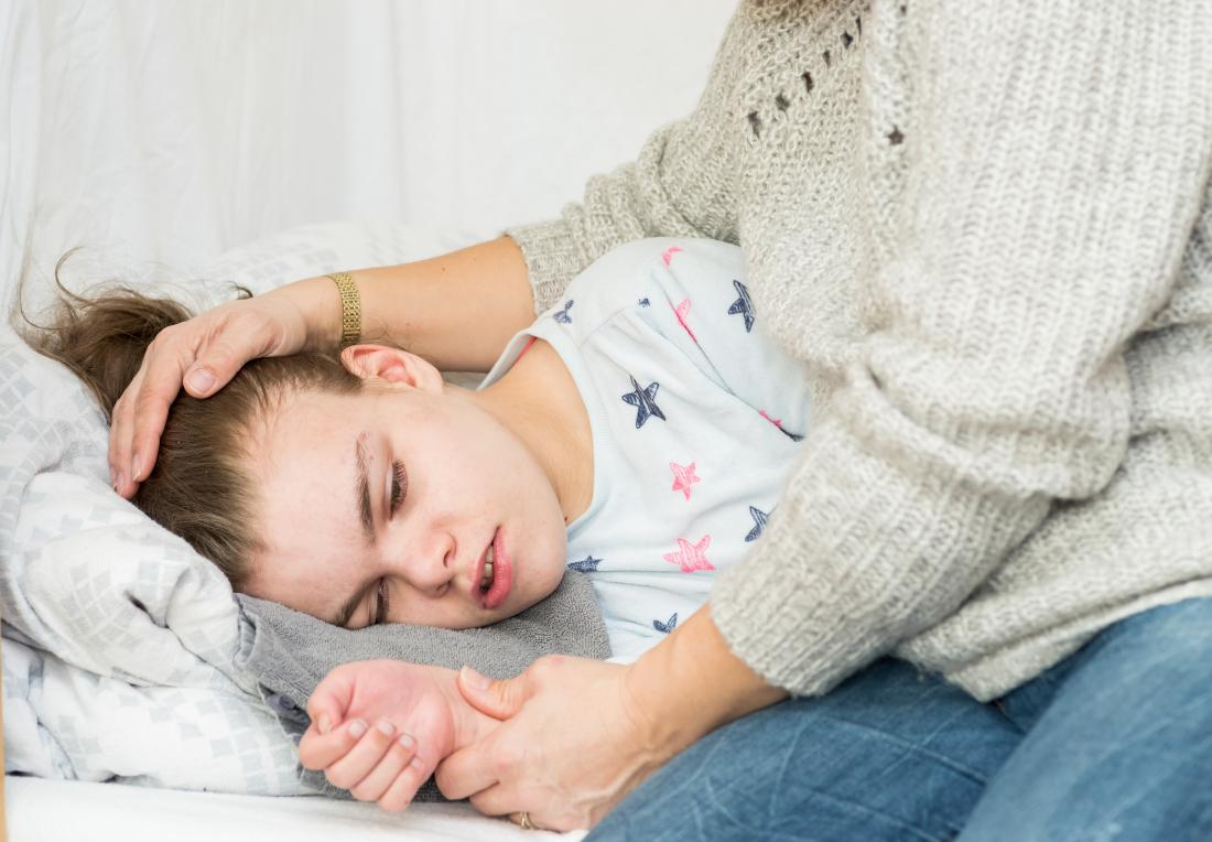 Child on bed with epileptic seizures and convulsions placed in the recovery position.