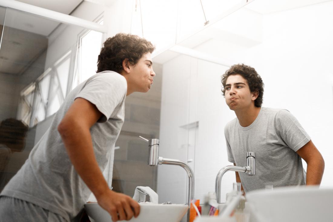 young man using mouthwash