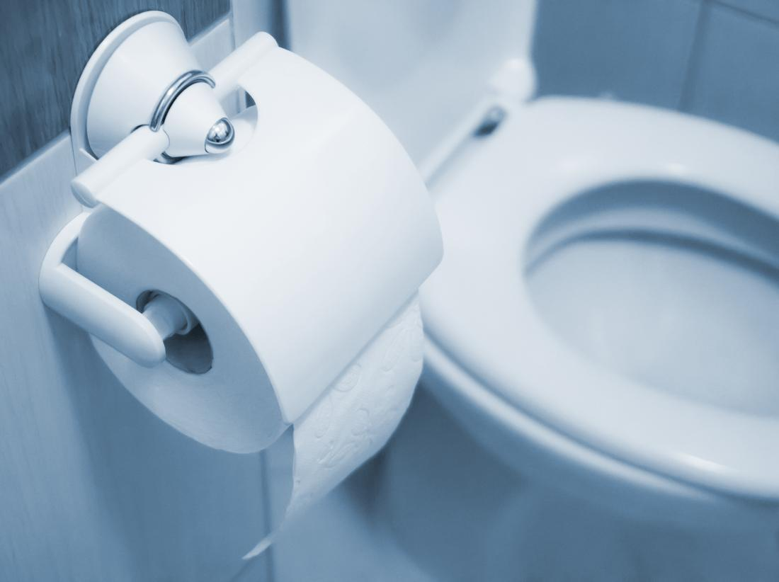 Toilet roll in foreground with toilet in background for rectal pressure
