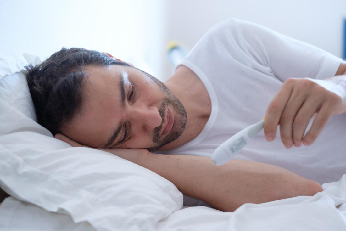 man with fever temperature lying in bed looking at thermometer