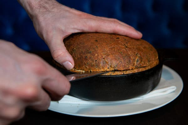 Slicing open a loaf of seaweed bread reveals something baked inside: a whole sweet potato.