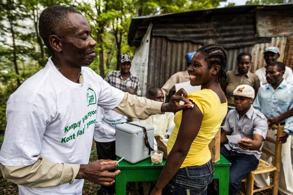 Volunteers providing vaccinations in Haiti as part of the GAVI project, which has helped vaccinate more than 760 million children by negotiating lower prices with manufacturers.