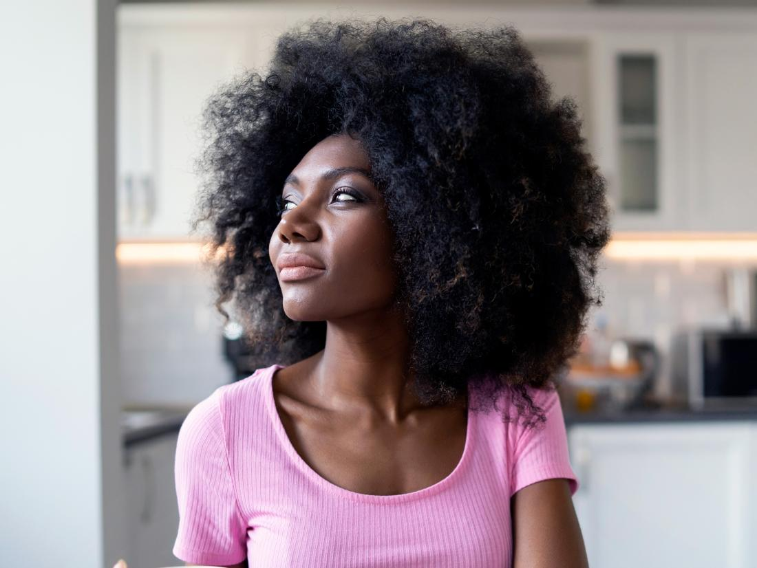 a woman looking pensive in her kitchen as she thinks if her Vestibular papillomatosis are of any concern.