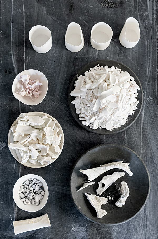 Moore's china cups, plates and bowls for Blue Hill at Stone Barns, made from cow bones, seen here in various stages of processing.